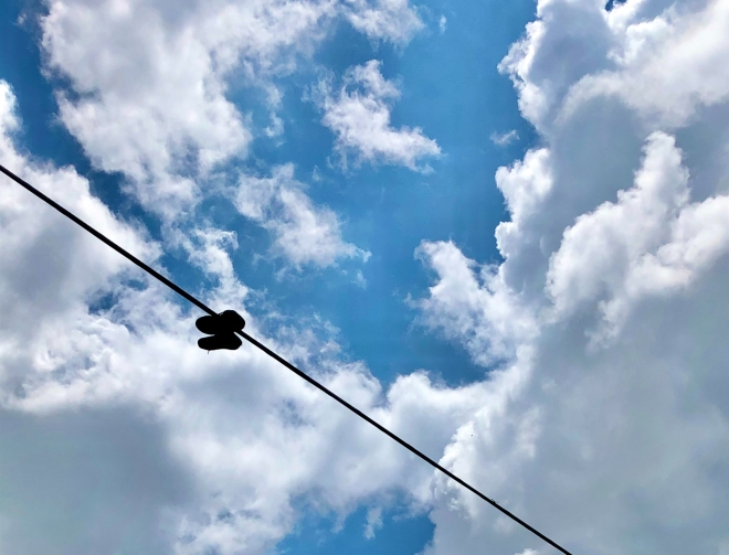 a blue sky with white clouds and sneakers hanging on a line